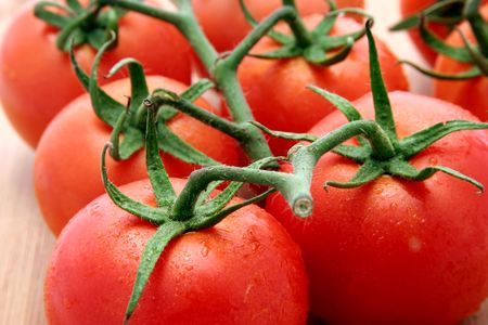 Fresh vine rippened truss tomatoes on a wooden chopping board Stock Photo