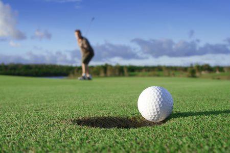 Ein Golfball nur um zu gehen in das Loch von einem langen Putt