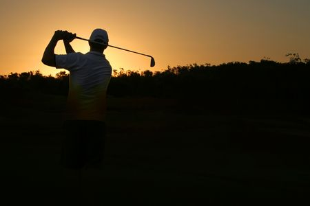 Golfer silhouette on golden sunset with black copy space Stock Photo