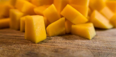 Chopped butternut squash looks like mango texture and color on wood cutting table