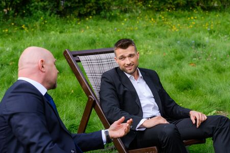 Businessmen are sitting in chairs and talking on grass outdoors Stock Photo