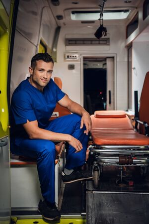 Happy paramedic sits in the ambulance car on the background