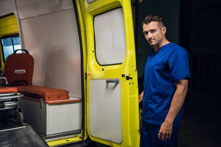 Corpsman in blue uniform stands and looks at camera in the ambulance car
