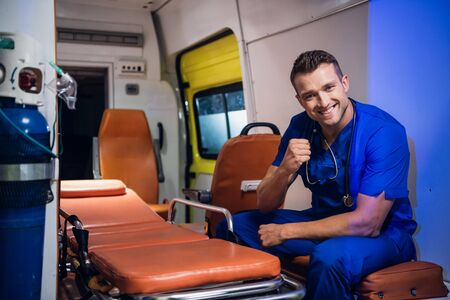 Young corpsman in uniform sits in the ambulance car and smiles