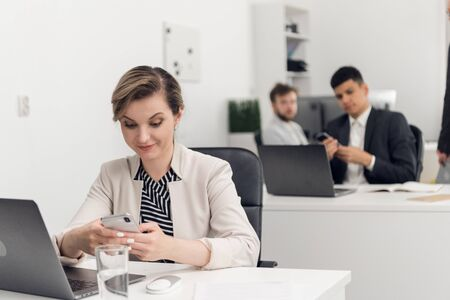 Young woman looks at her phone surprisingly in the office, her colleages sit a a tables beside her Фото со стока