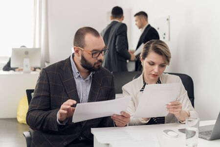 Man and woman are holding documents in their hands and searching something in them in the office