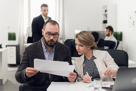 Woman and man sit at a table with documents and discuss them in the office