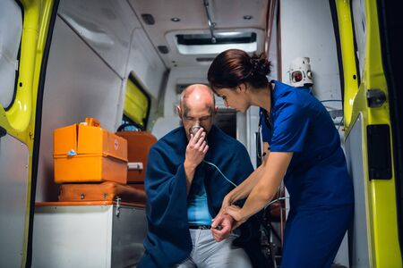 Man sits with oxygen mask, woman in medical uniform holds his hand