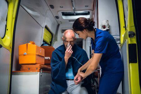 Mann sitzt mit Sauerstoffmaske, Frau in medizinischer Uniform hält seine Hand
