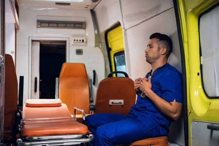 Corpsman in uniform sits and holds stethoscope in his hands inside the ambulance car