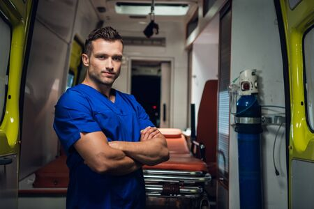 Young paramedic look at camera and smile, ambulance car on the background Stock Photo