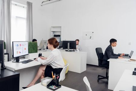 Man in suits and woman in skirt sit at a tables, they are busy with work in the office