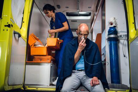 Man breathe through oxygen mask, doctor in uniform picks a medicine in a syringe in the ambulance car