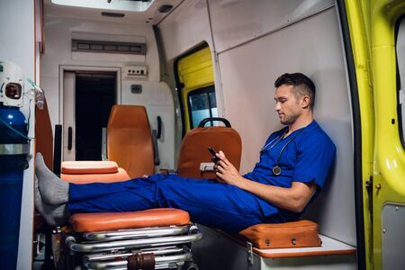 Young corpsman in uniform sits with phone in the ambulance car