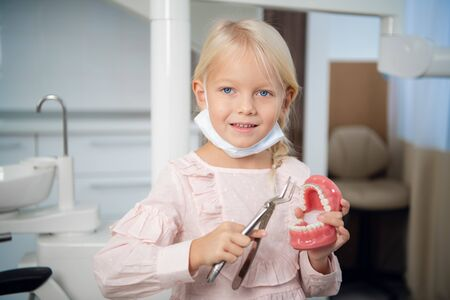 A little blond girl playing a dentist in the clinic