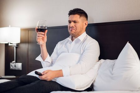 A drunk man with a glass of wine in bed, watching soap opera and crying