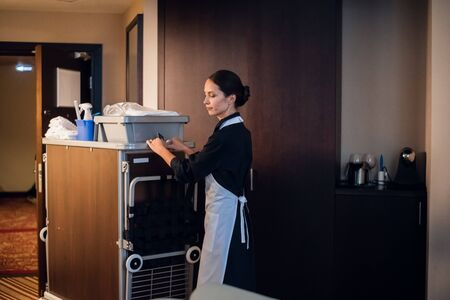 A hotel maid in a uniform cleaning the rooms in a hotel Reklamní fotografie