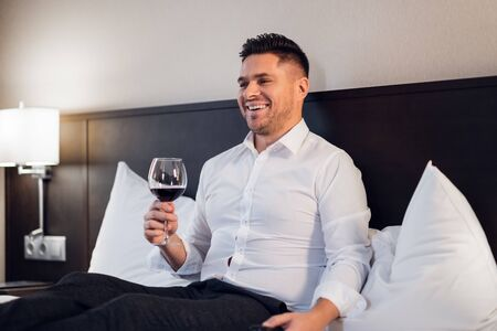 Relaxed businessman having a glass of wine in his hotel room after a tiring day