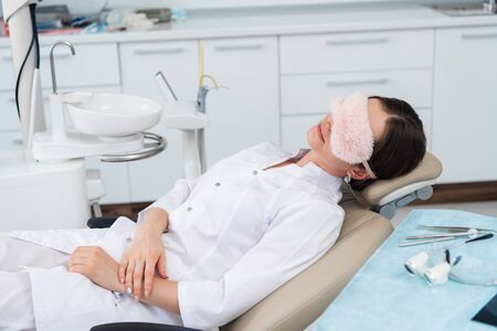 After hours in the dental clinic. A doctor is relaxing in her sitting after a tiring day
