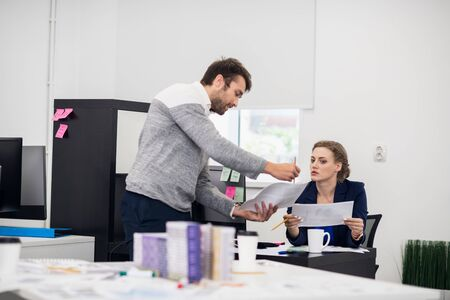 Two office workers, a man and a woman, discussing something. The