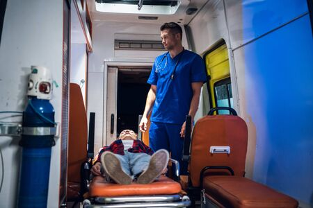 Unconscious woman lying on a stretcher in an ambulance car, a paramedic providing her first aid