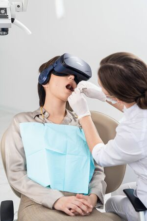 The dentist is working on the treatment of cavities, while her patient is wearing the VR glasses