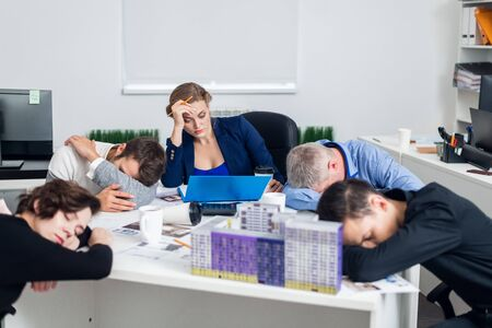 Bored or tired business people sleeping, resting on their workplace during the meeting, a concept of exhausted businesspeople bored, asleep, tired Banque d'images