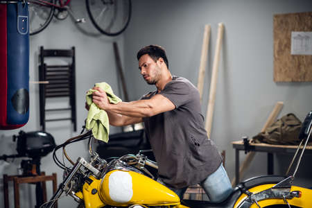 A strong male biker repairs his motorcycle in the garage. Interior of the workshop.