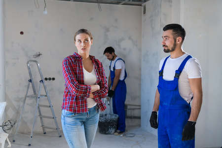 The woman is disappointed with the way the foreman renovates the apartment
