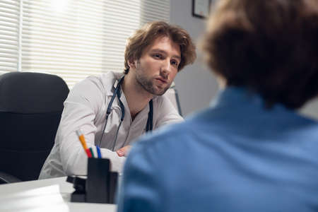 Healthcare and medicine concept - a doctor with his patient in a consultation room