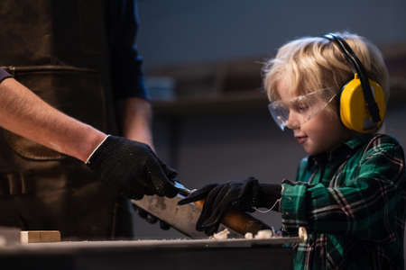 an experienced carpenter gives his little assistant carpentry tools in the workshop.