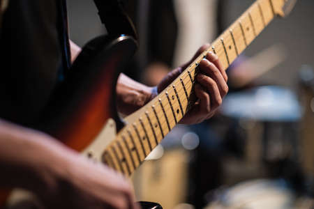 close-up of the hands of a musician playing an electric solo guitar in the Studio
