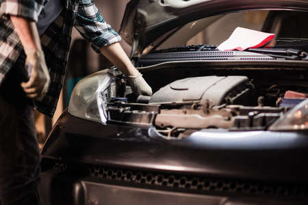 a young male car mechanic in a shirt and gloves checks the engine oil level in a black car