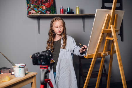 a cute teen artist is recording a story for her video blog in a workshop at an art school
