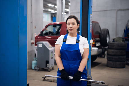 Mechanic in working overalls holds a tool in her hands