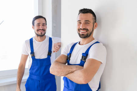 Two bearded men in blue uniforms posing for a photo