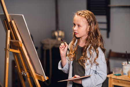 Young girl creative artist at work in a workshop. With passion draws a picture immersed in work
