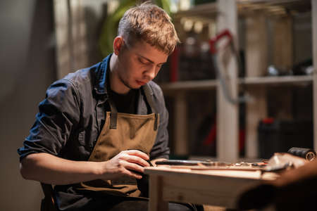 a young apprentice makes blanks for the production of shoes in the workshop