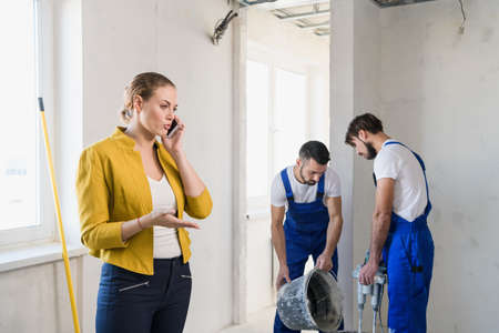 Two workmen are preparing cement in a bucket. Woman speaks seriously on the phone Imagens