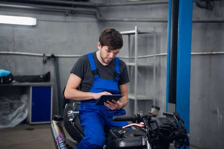 A mechanic in work clothes is sitting on a motorcycle. He uses a tablet