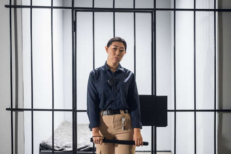 A young prison guard poses in front of prison bars in uniform. In a maximum security prison. Banque d'images