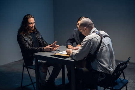 In the police stations interrogation room, good and bad cops are questioning a theft suspect in a leather jacket