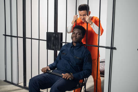 A black prison guard sits in front of cages with dangerous criminals on a chair with a baton