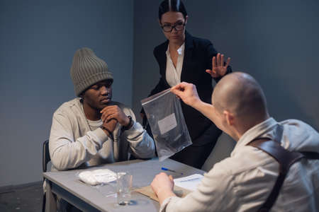 An experienced investigator during the interrogation shows the alleged criminal and his lawyer evidence of the crime committed.