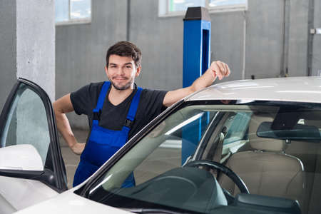 A man in work clothes is standing next to a white car