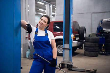 Woman in working overalls holds a wrench in her hands and looks at the camera