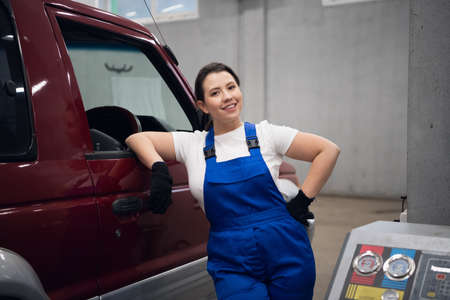 A craftswoman in work clothes is standing at the car and looking at the camera