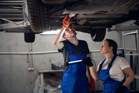 A workman and a female repairer check the suspension from below the machine. They use a torch Foto de archivo