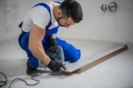 A bearded repairer in overalls marks the board with a pencil and uses a jigsaw