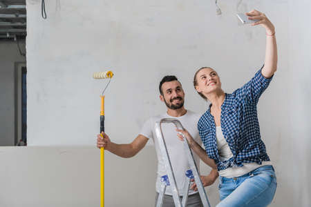 Married couple taking selfie on the background of the wall with a stepladder and roller